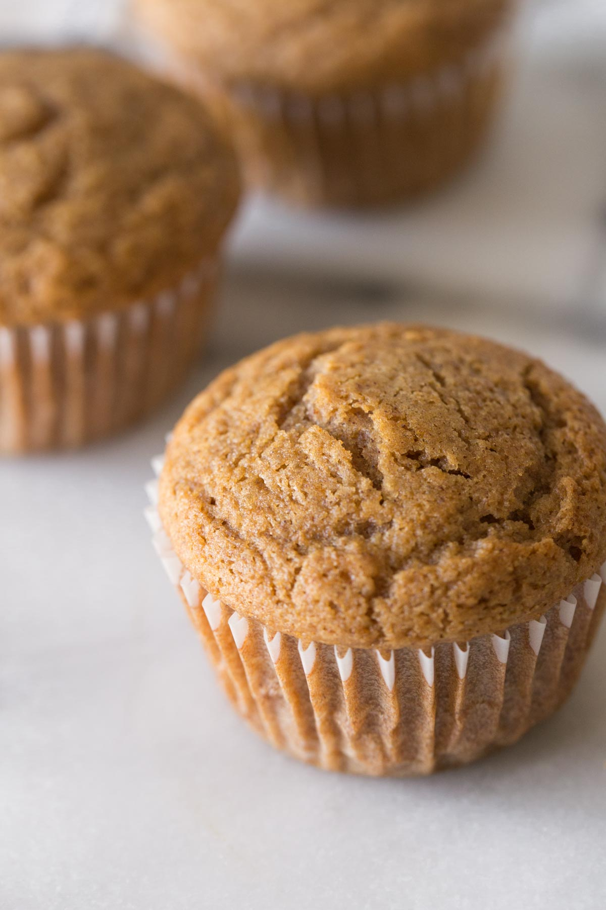 A close up view of the top of a Cinnamon Applesauce Muffin on a white background.