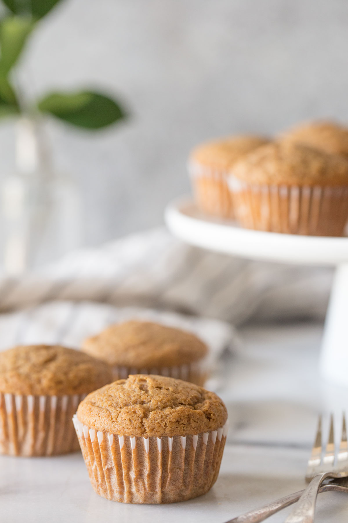 Cinnamon Applesauce Muffins on a white marble board with a cake stand in the background.