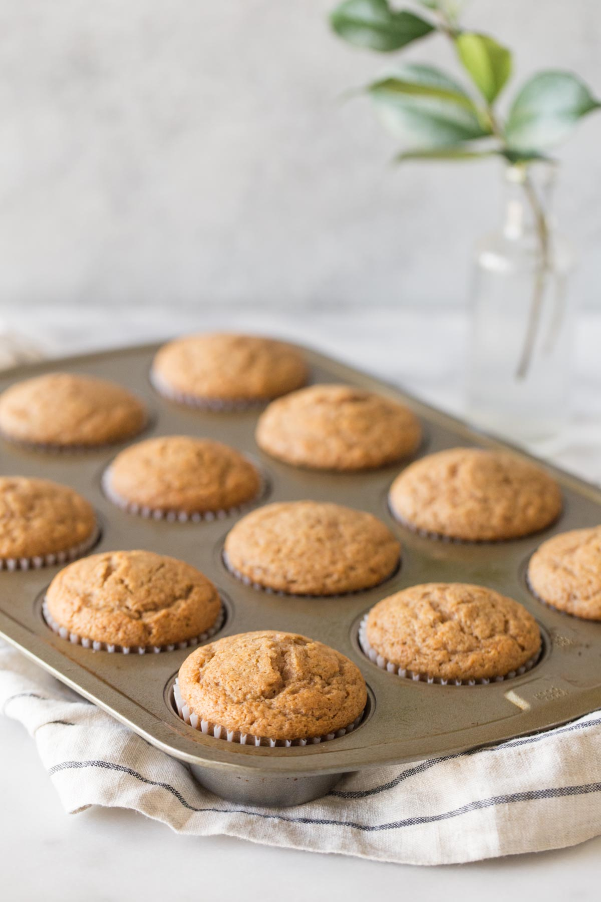 A muffin tin full of Cinnamon Applesauce Muffins with a white marble background.