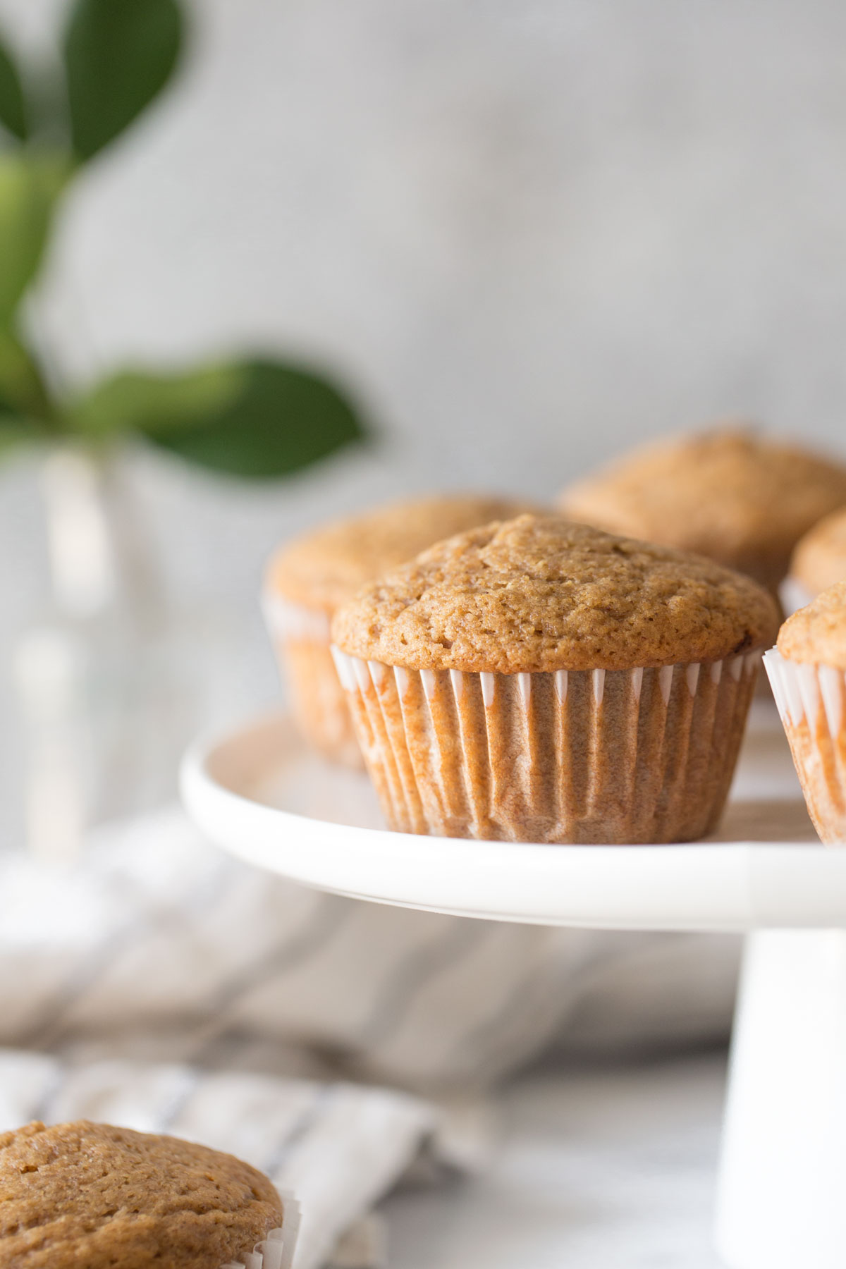 Cinnamon Applesauce Muffins on a white cake stand with a white background.