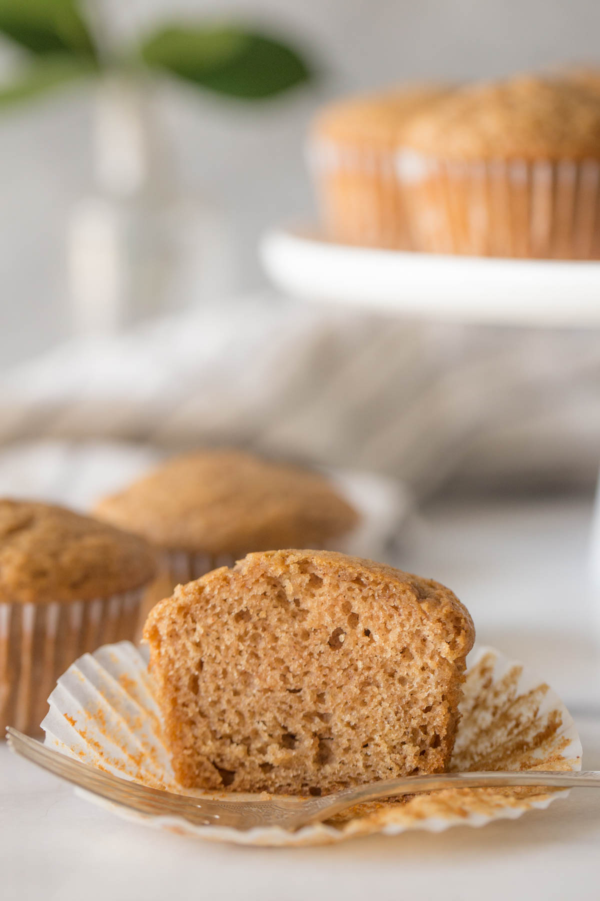 A close up view of a halved Cinnamon Applesauce Muffin on a white background.