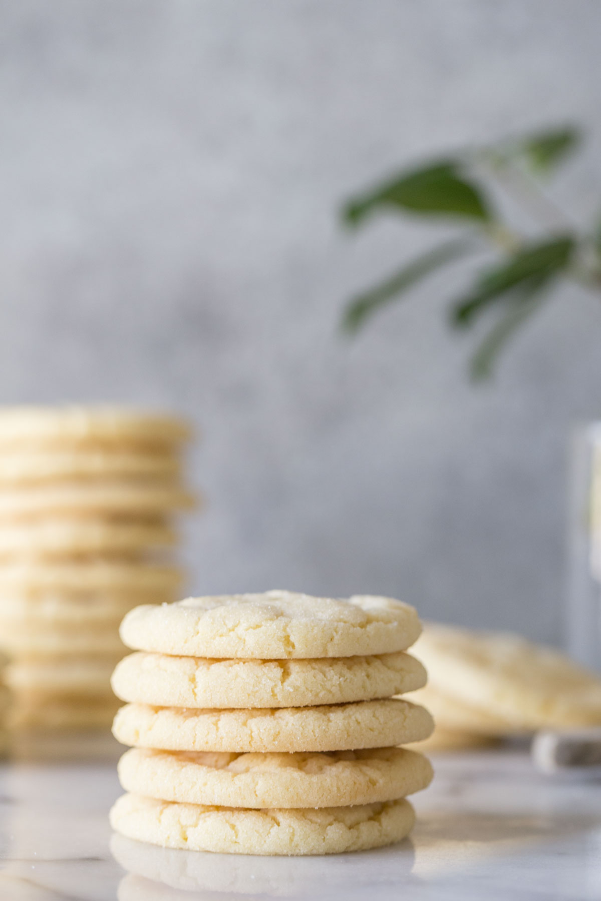 Stack of Soft and Chewy Sugar Cookies on a white and grey background.