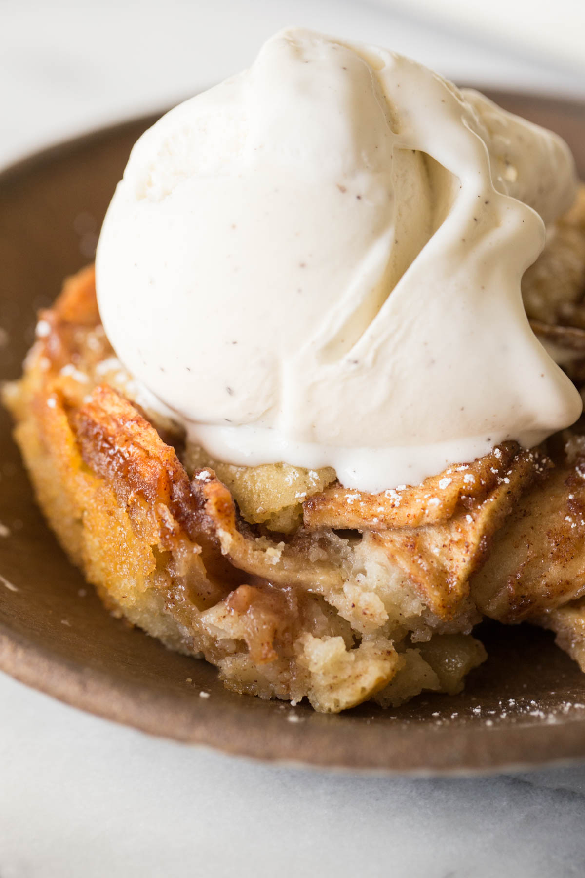 Close up view of bowl full of Apple Cobbler with a scoop of vanilla ice cream on top.