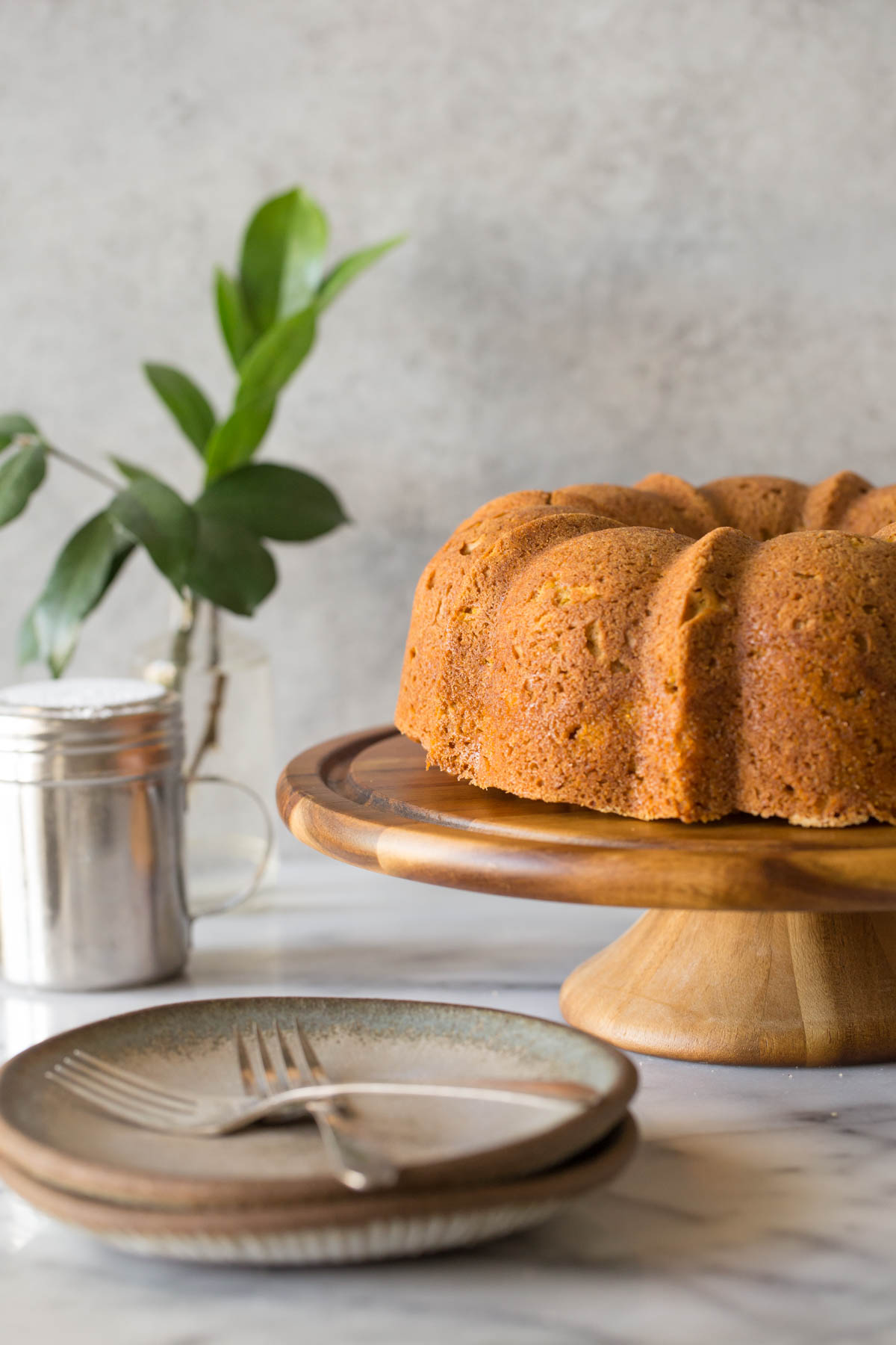 Apple Pumpkin Cake on a cake stand with a grey background.