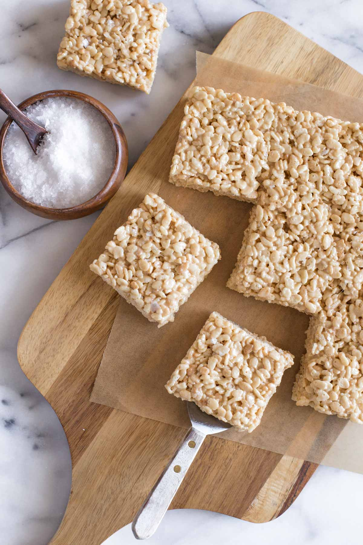 Overhead view of Salted Caramel Rice Krispie Treats on a wooden cutting board.