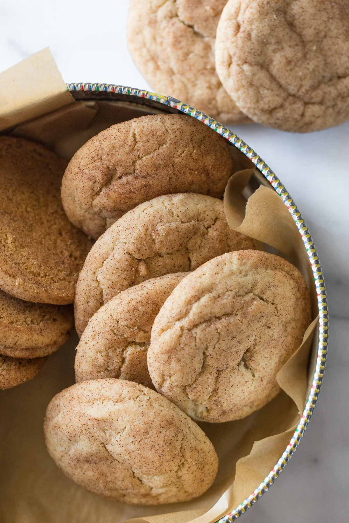Overhead view of Super Soft Snickerdoodles in a cookie tin lined with parchment paper.