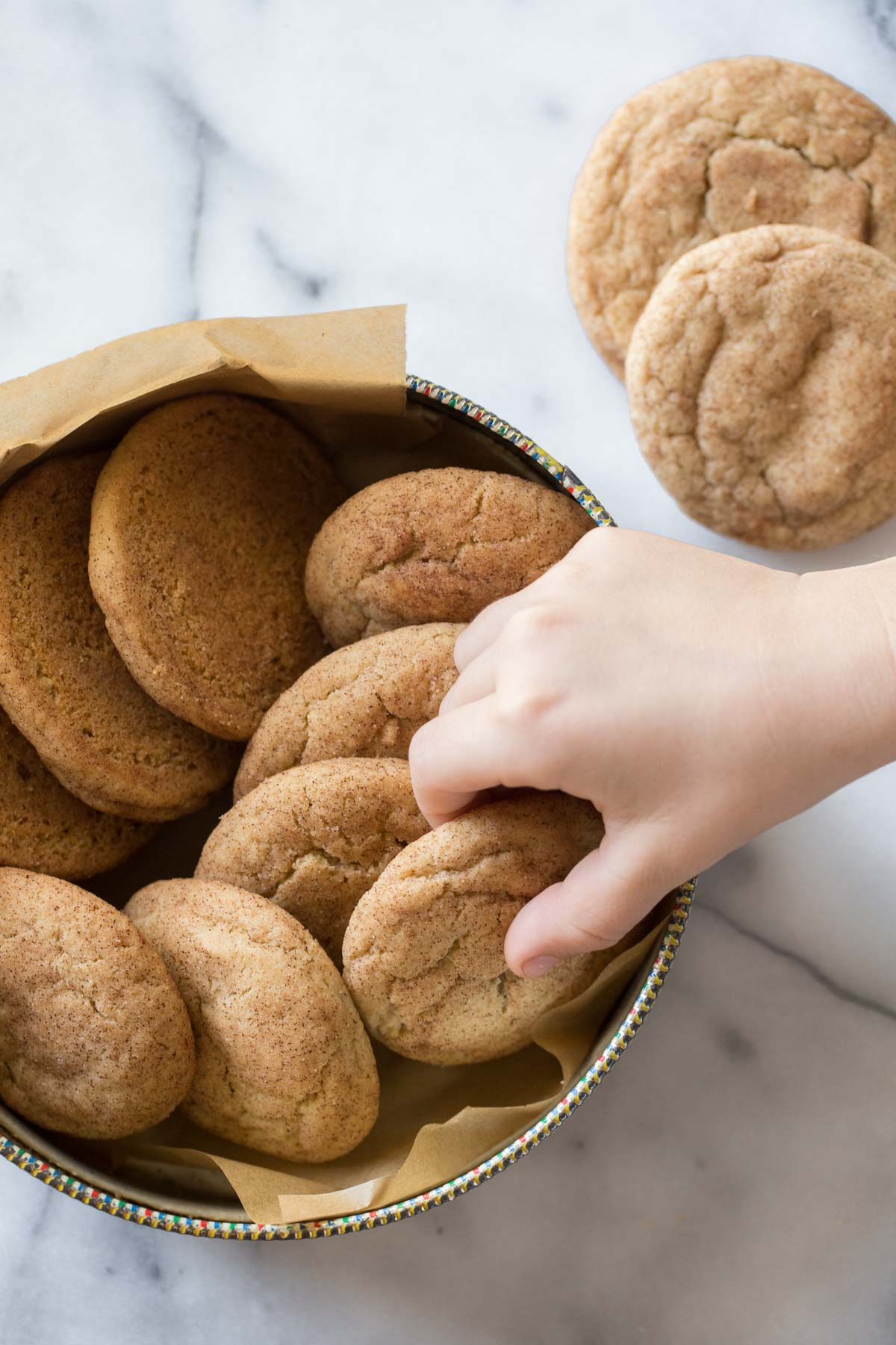 A child's hand reaching out to take a Super Soft Snickerdoodle cookie in a cookie tin on a white background.