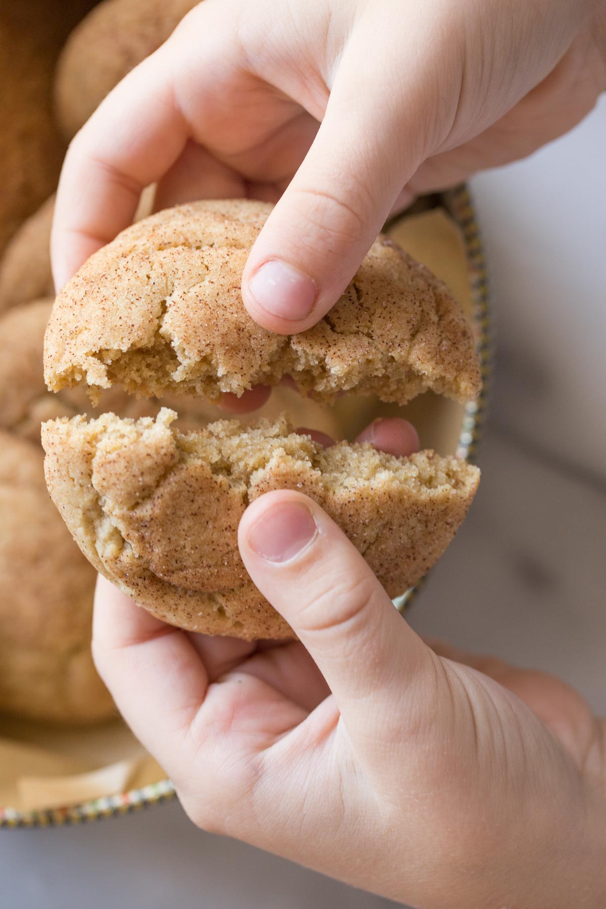 A child's hand breaking open a Super Soft Snickerdoodle.