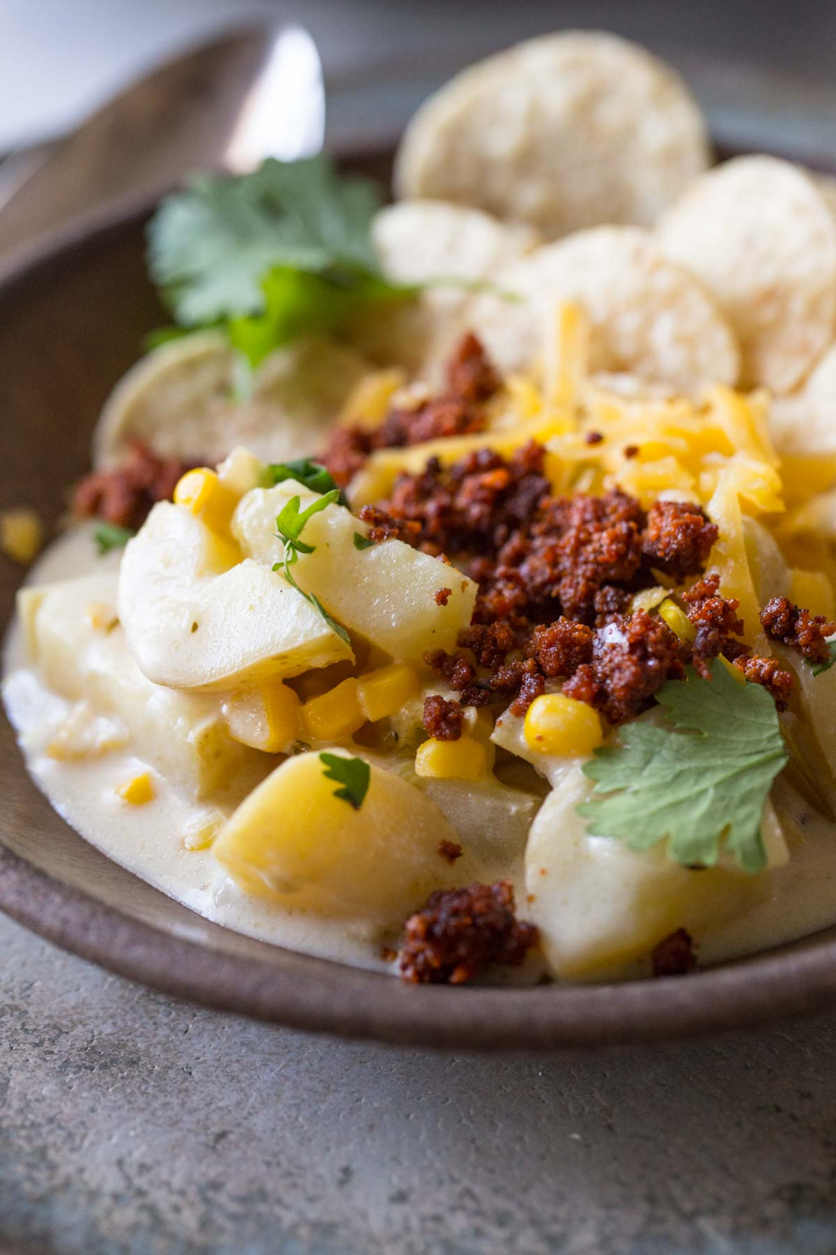 Close in shot of Creamy Corn Chowder With Chorizo, topped with cilantro and cheese.