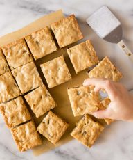 Overhead view of blondies with a child's hand taking one.