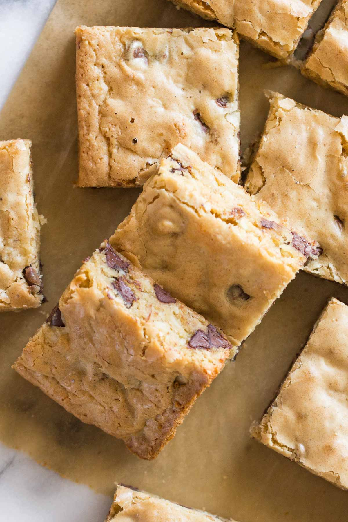 Close up overhead view of cut up blondies on parchment paper.