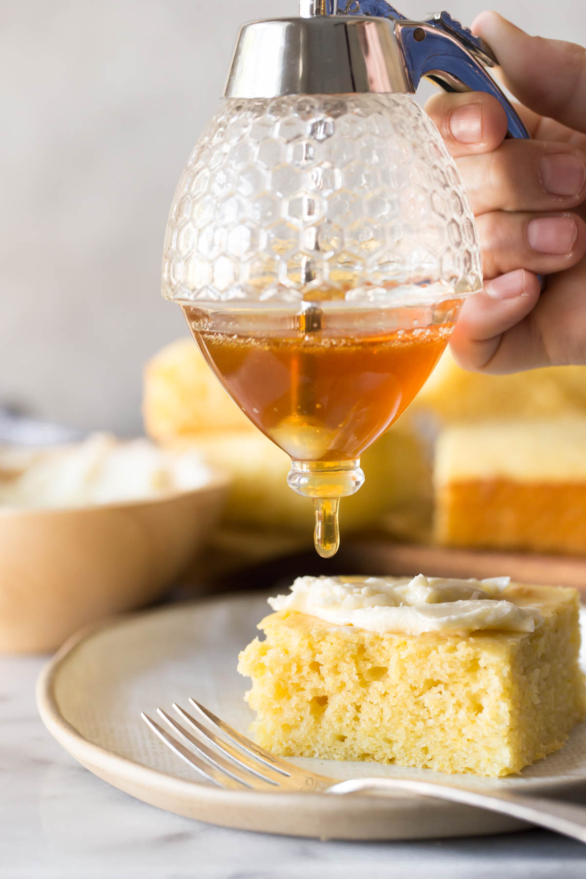 Honey drizzle over a slice of Easy Homemade Cornbread on a plate with fork in foreground.