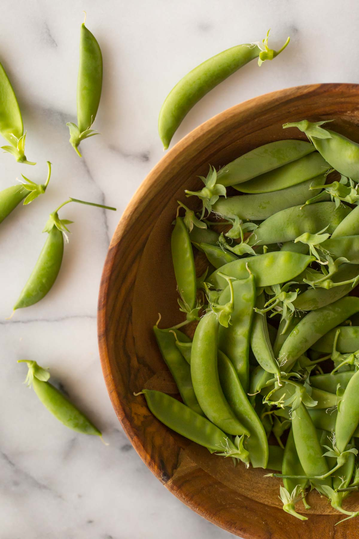 Overhead shot of a wooden bowl full of sugar snap peas on a white marble background.