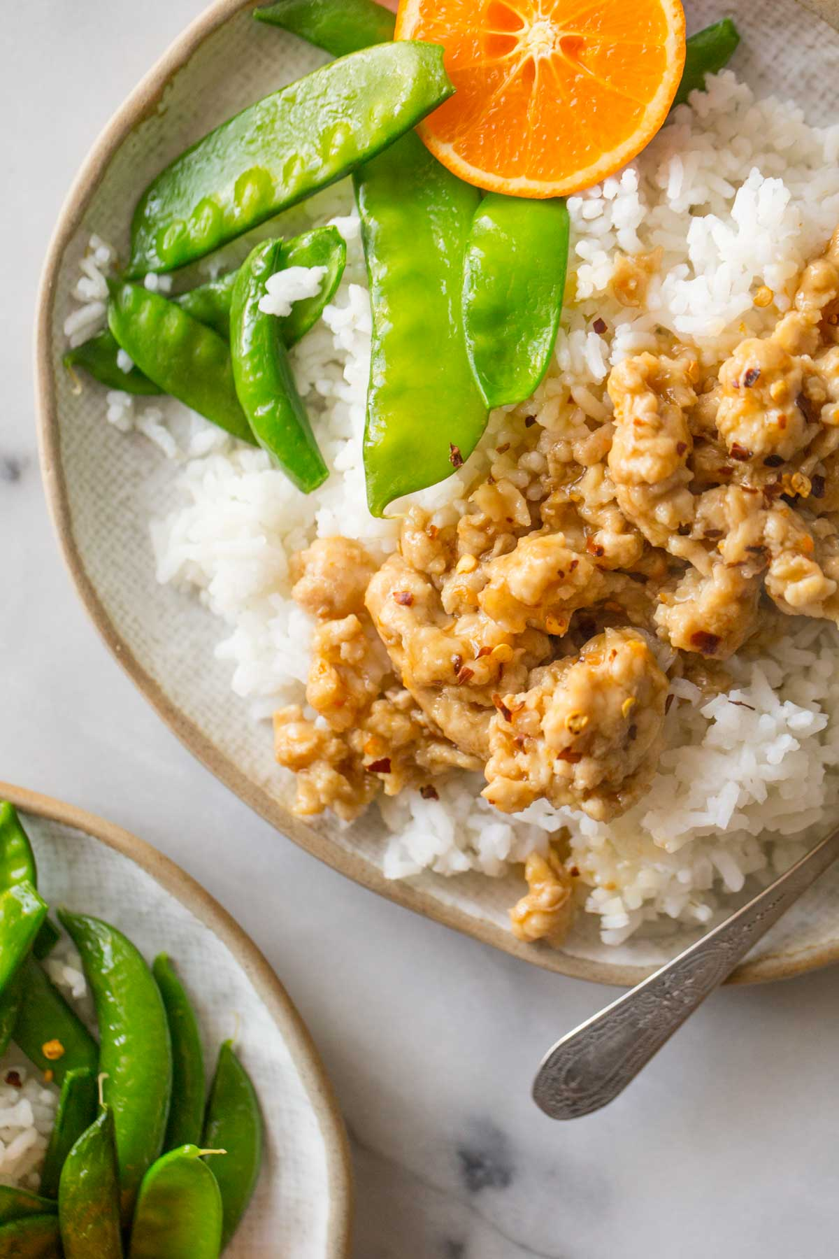 A close up overhead shot of Easy Orange Chicken over rice with snow peas.