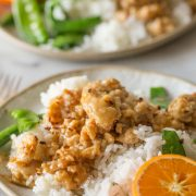 Two plates of Easy Orange Chicken with white rice and snow peas.