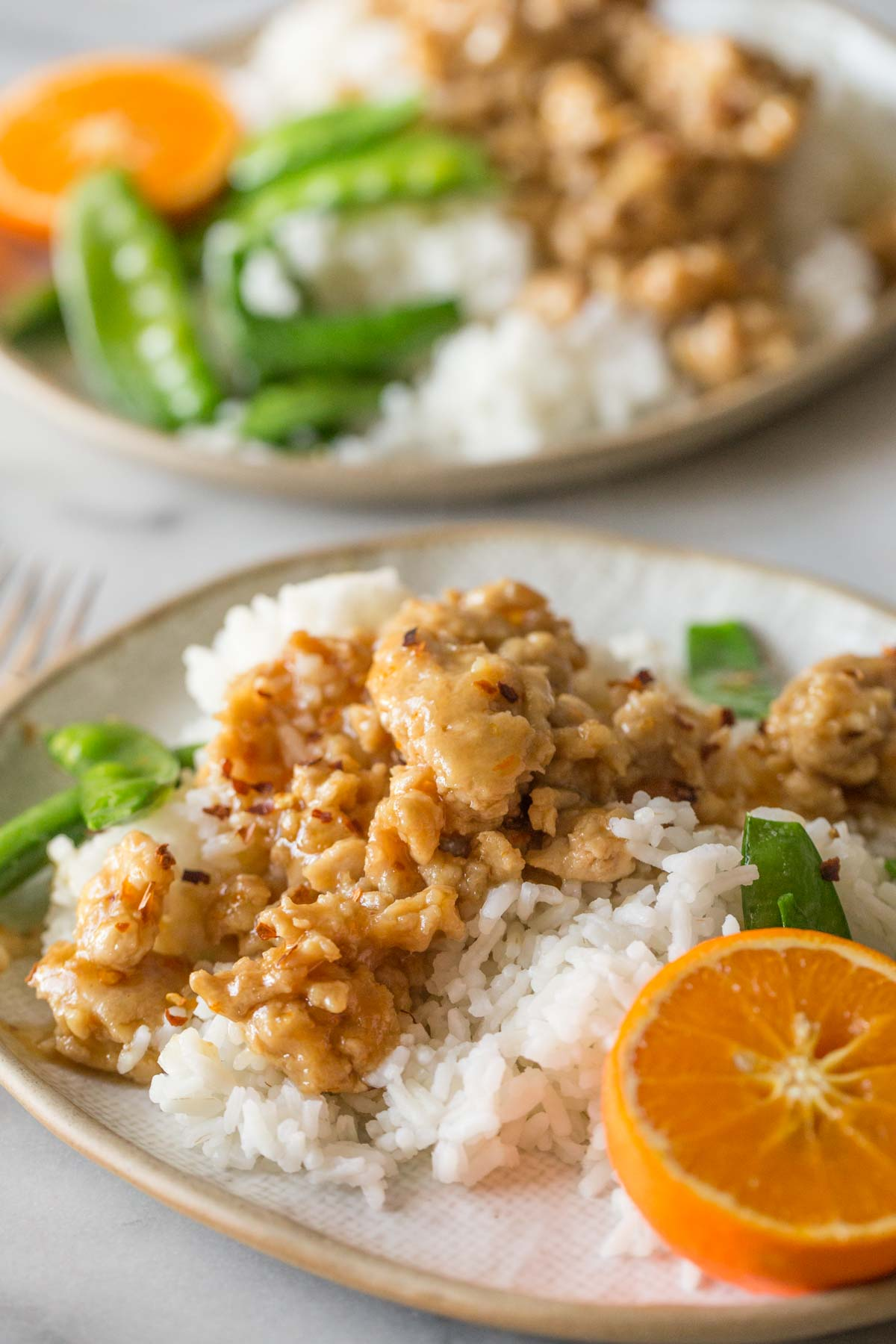 Two plates of Easy Orange Chicken on a white background.