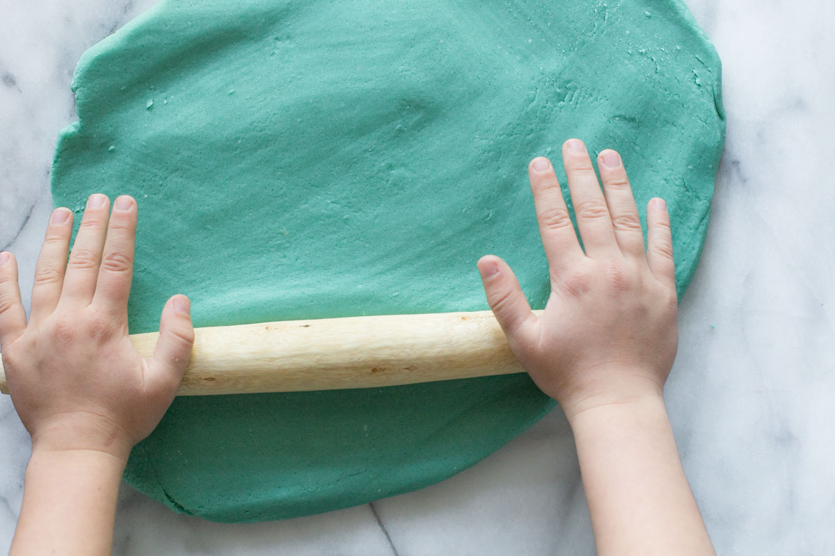 Overhead view of blue playdough being rolled out.