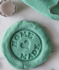 Blue homemade playdough with the words home made stamped into it.