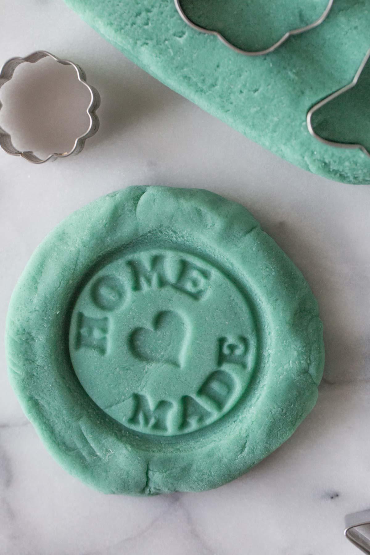 A close-up view of blue playdough with a homemade stamp pressed into the dough.