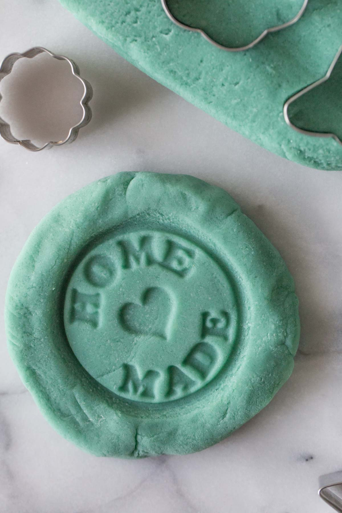 A close-up view of blue playdough with a homemade stamp pressed into the dough.