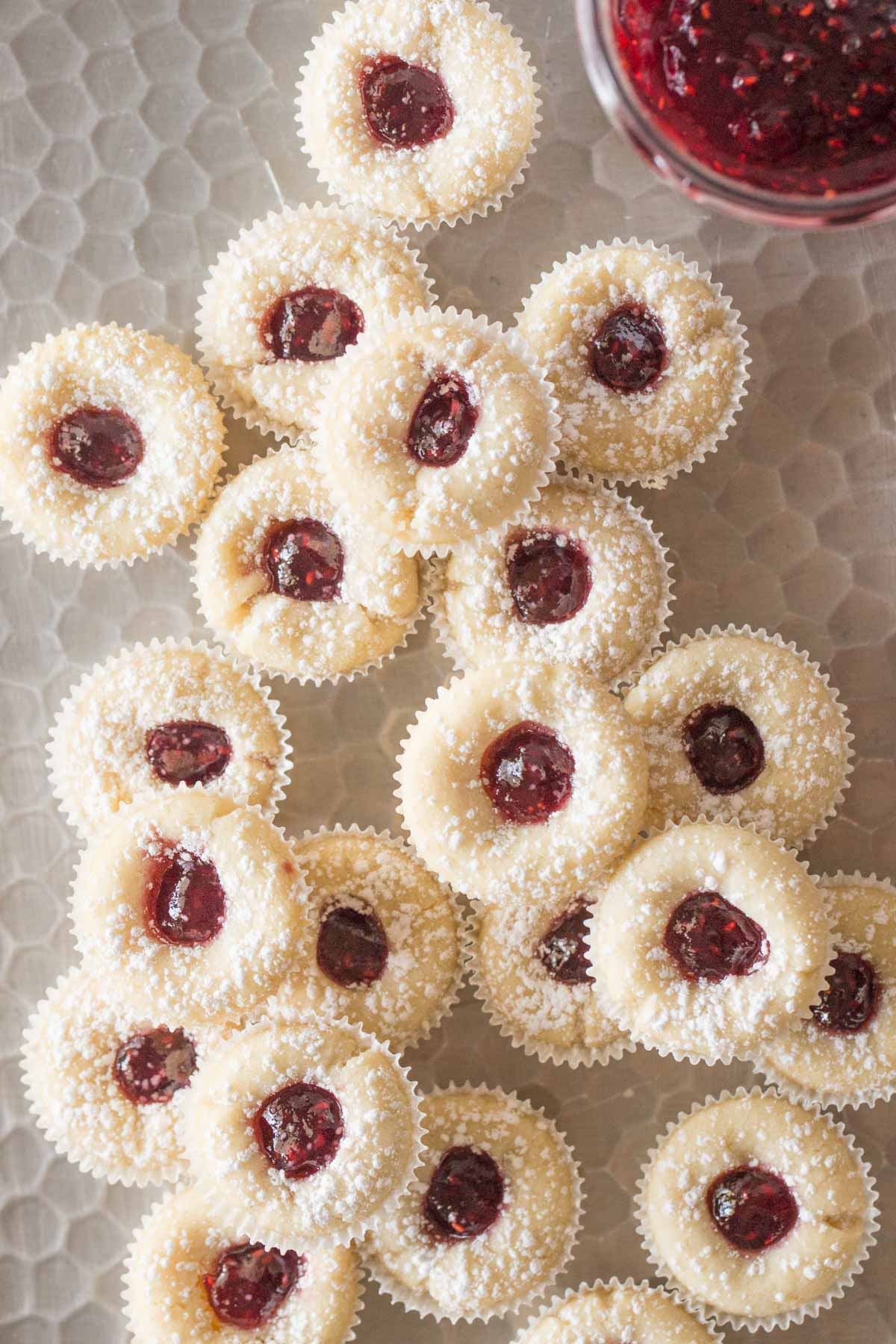 Overhead view of Mini Raspberry Almond Tarts with powdered sugar on a silver tray.