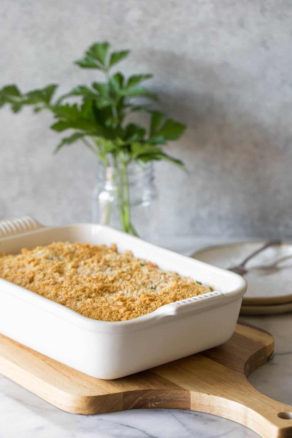 Cooking casserole dish on a wooden cutting board.