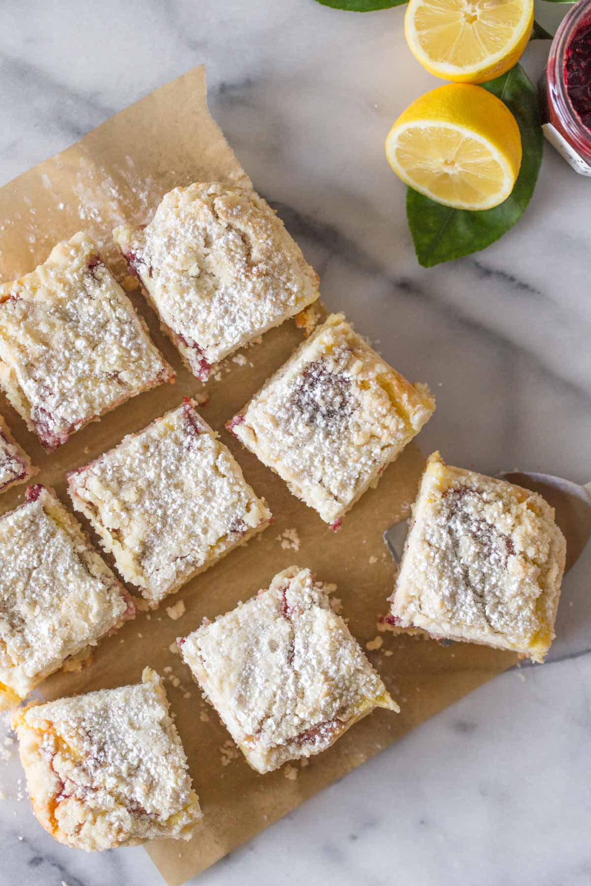 Overhead shot of cut pieces of Lemon Raspberry Cream Cheese Coffee Cake on a piece of parchment paper on a marble slab.