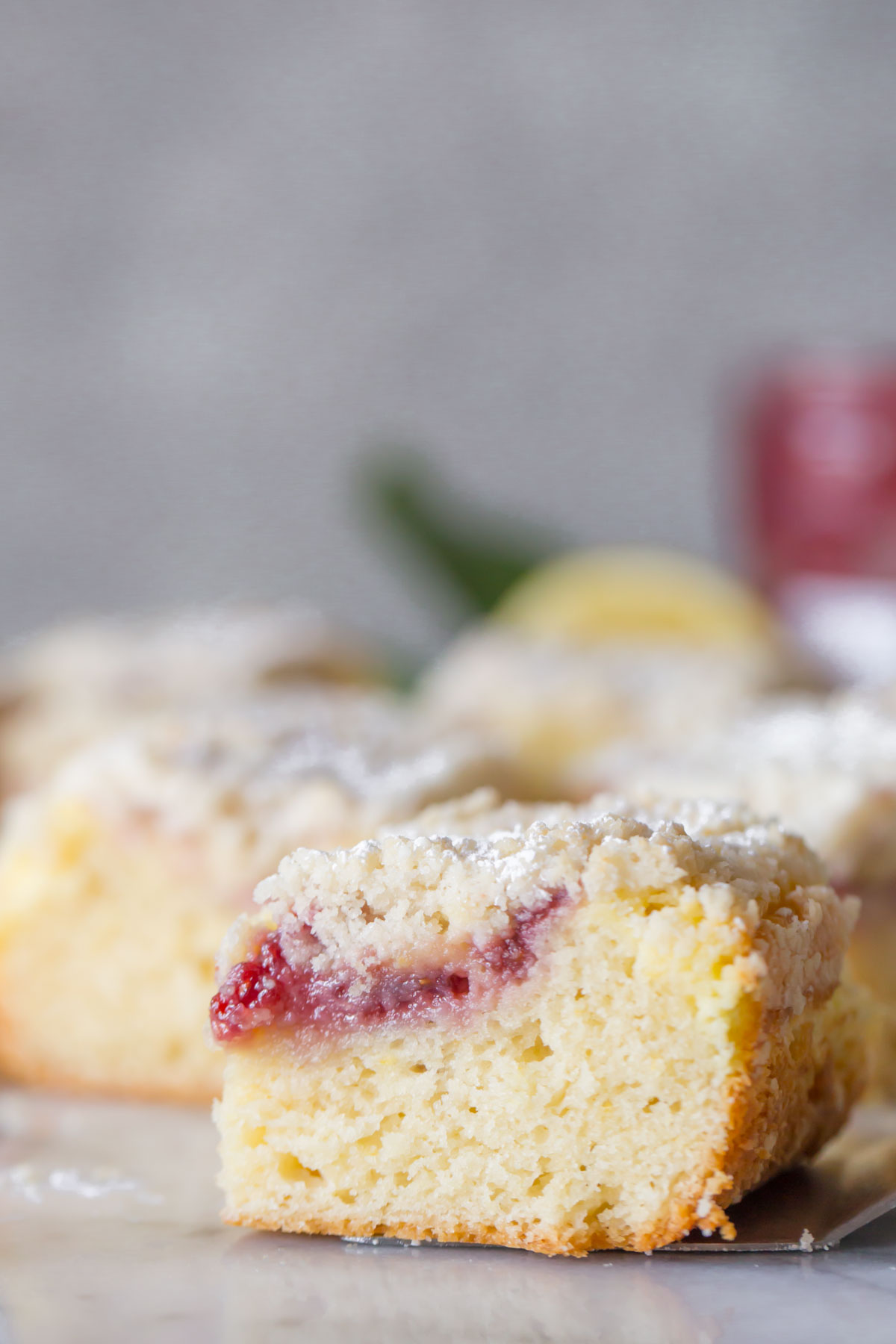 Close up shot of sliced Lemon Raspberry Cream Cheese Coffee Cake on a marble background.
