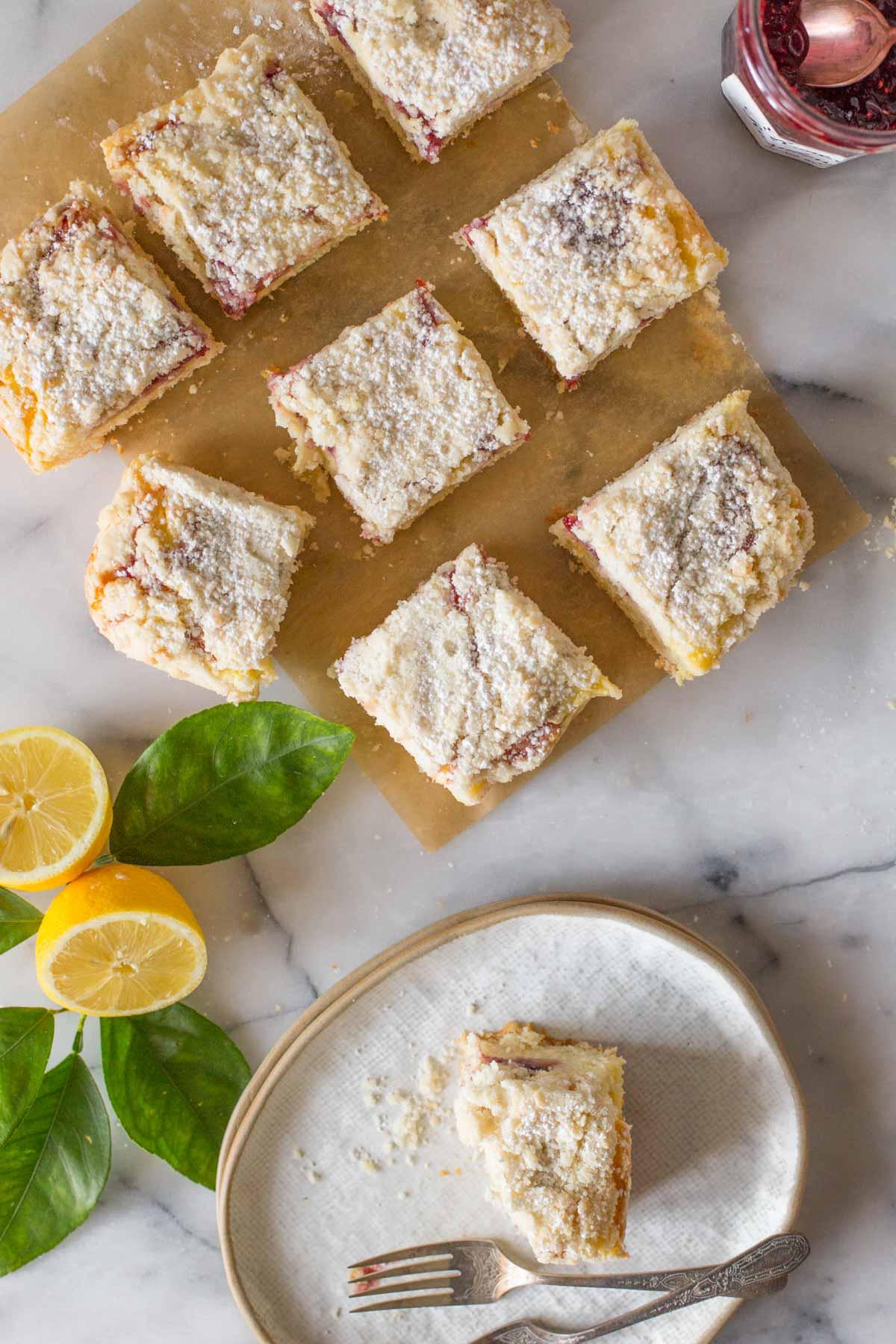 Overhead shot of cut pieces of Lemon Raspberry Cream Cheese Coffee Cake with fresh lemons.