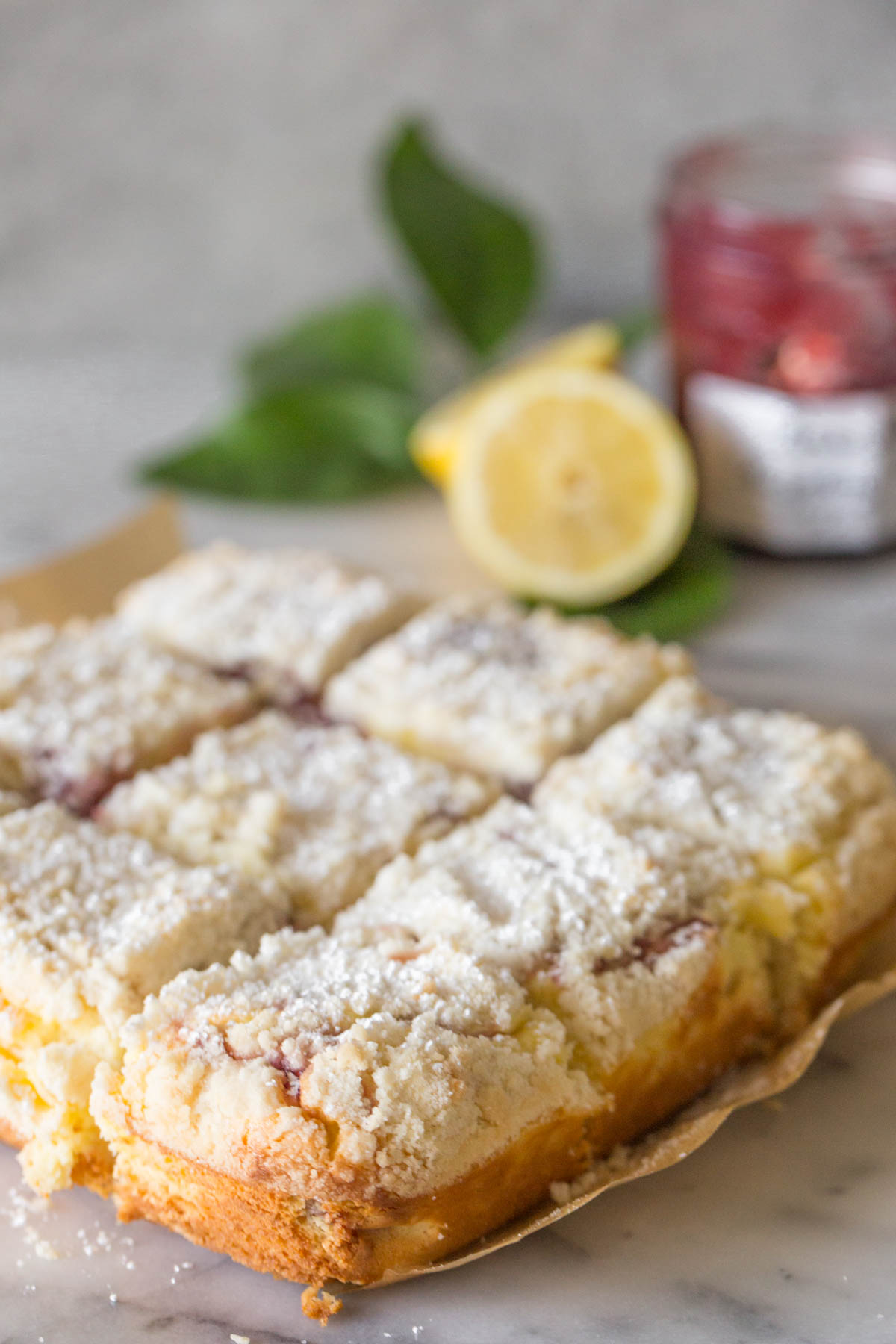 Lemon Raspberry Cream Cheese Coffee Cake dusted in powdered sugar with a grey background.