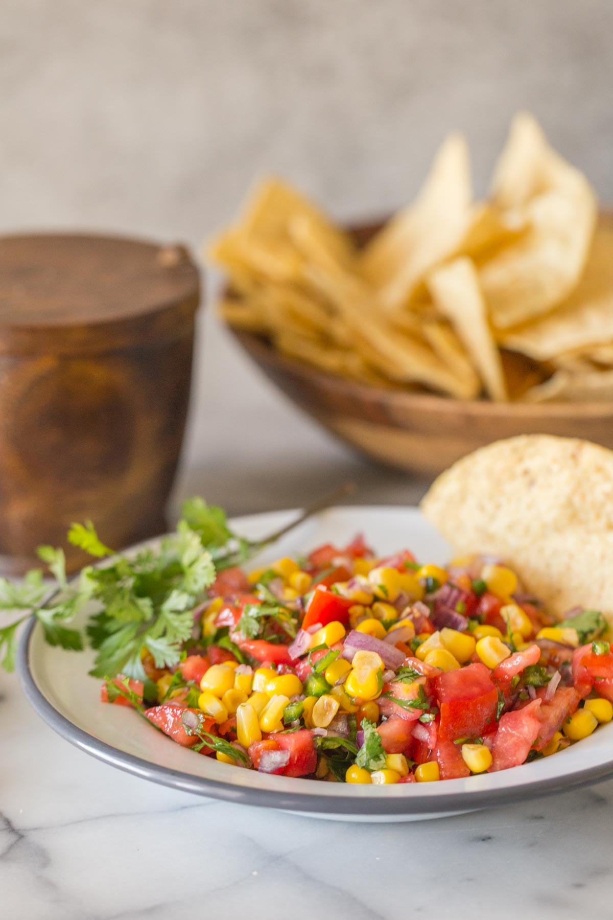 Close up of Homemade Pico de Gallo in a white bowl with chips.