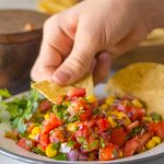 Chip scooping out Homemade Pico de Gallo.