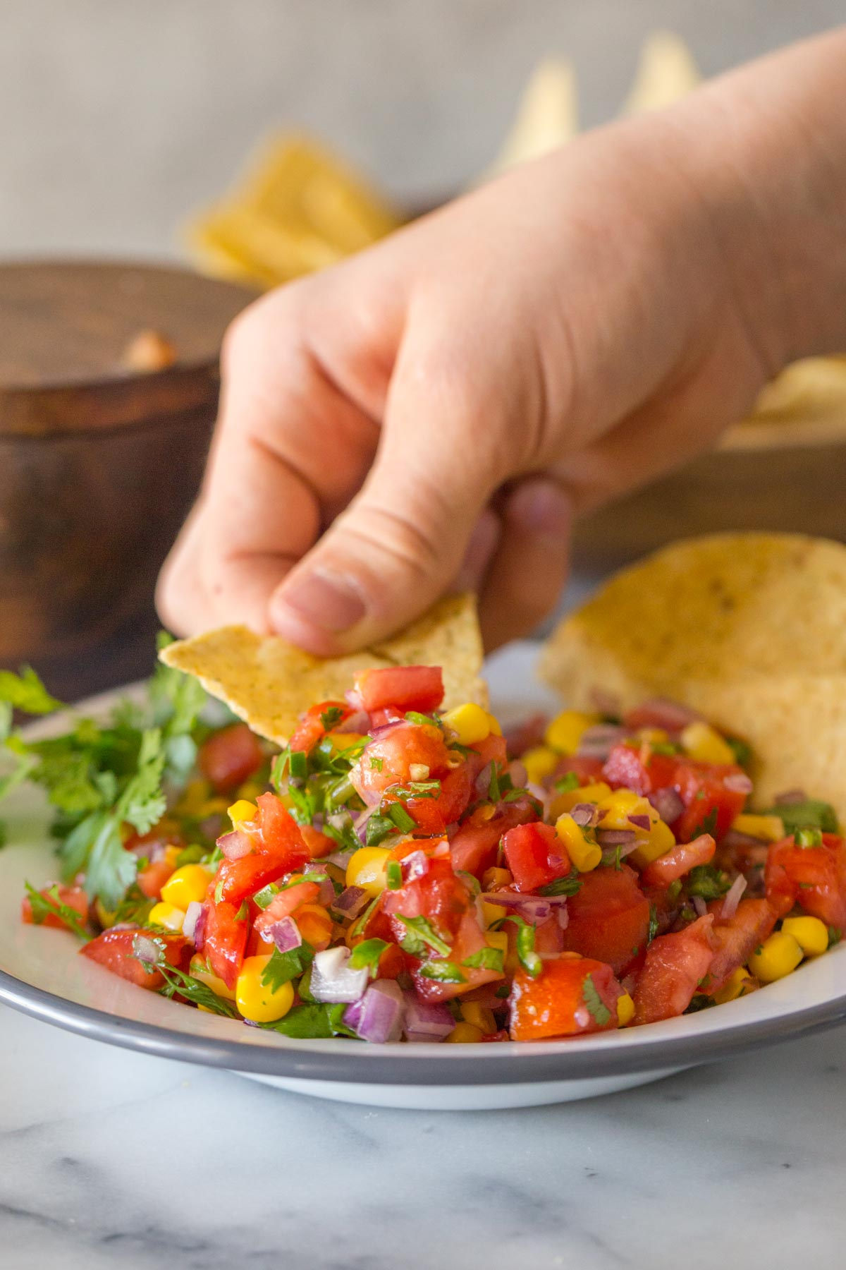 Chip scooping Homemade Pico de Gallo.