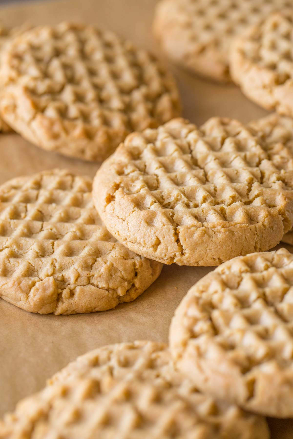 Soft and Chewy Peanut Butter Cookies spread out on a parchment paper baking sheet.