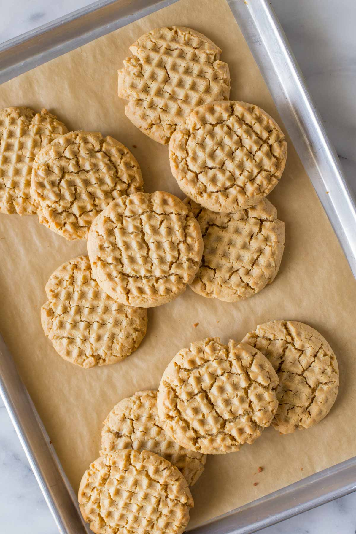 Overhead view of Soft and Chewy Peanut Butter Cookies on a parchment lined baking sheet.
