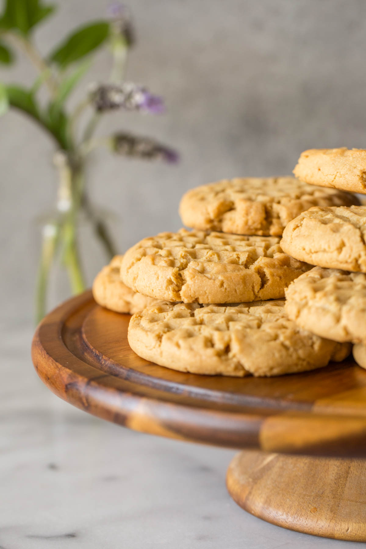Close up view of Soft and Chewy Peanut Butter Cookies on a cake stand with a grey background.