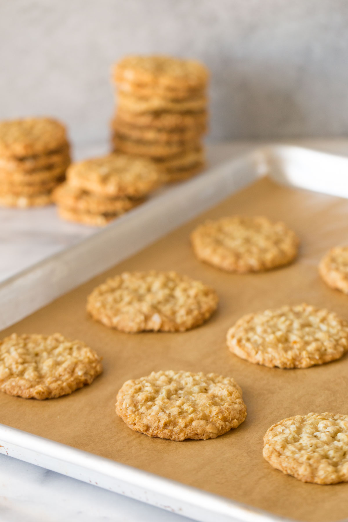 Buttery Coconut Oatmeal Cookies on a parchment paper lined baking sheet, with stacks of Buttery Coconut Oatmeal Cookies in the background.