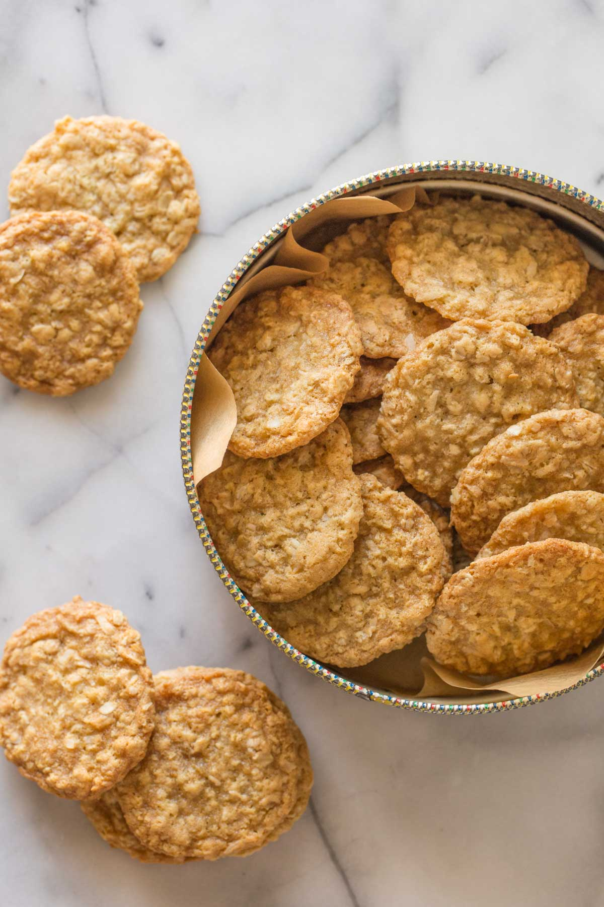 Overhead shot of Buttery Coconut Oatmeal Cookies in a container, with more cookies next to the container on a marble background.