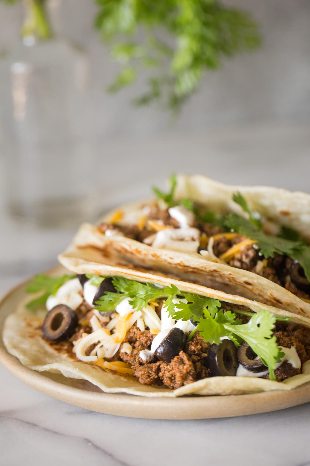 Close up shot of tacos with toppings and a grey background.