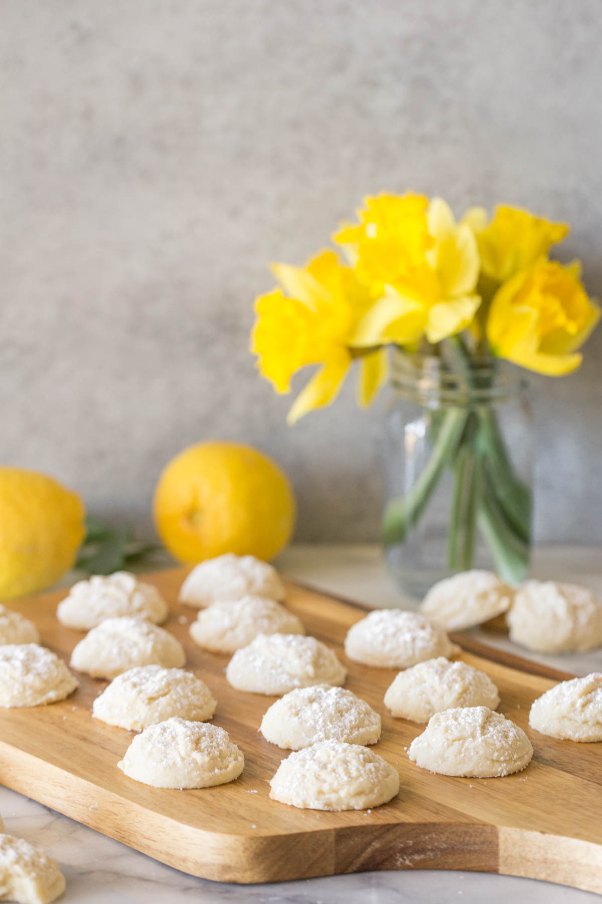 Lemon Cookies on a wooden cutting board with yellow daffodils in the background.