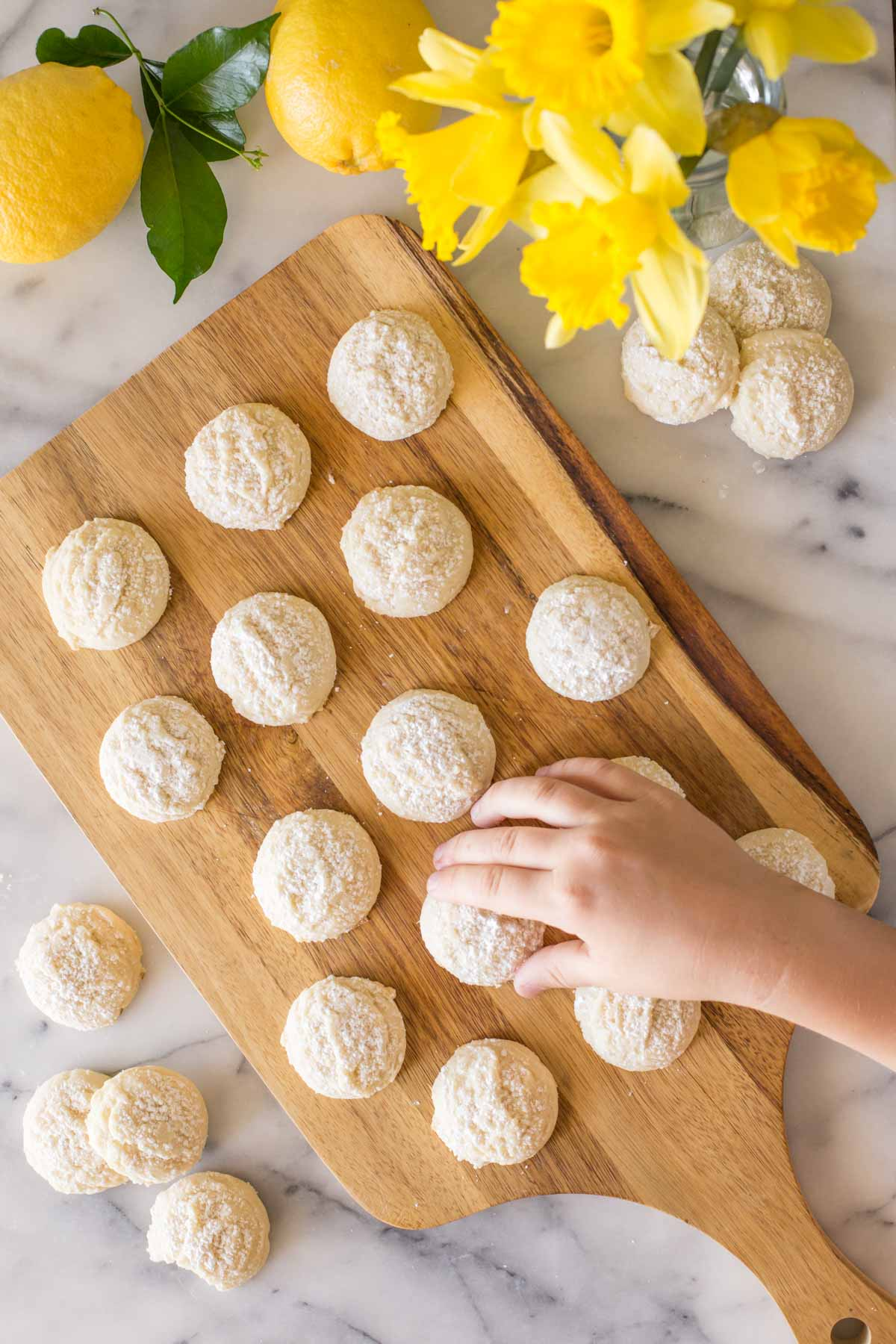 Hand reaching for Lemon Cookie on a wooden cutting board.