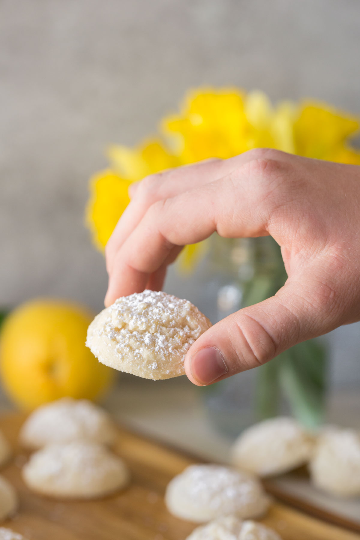 Hand holding Lemon Cookie with yellow daffodils in the background.