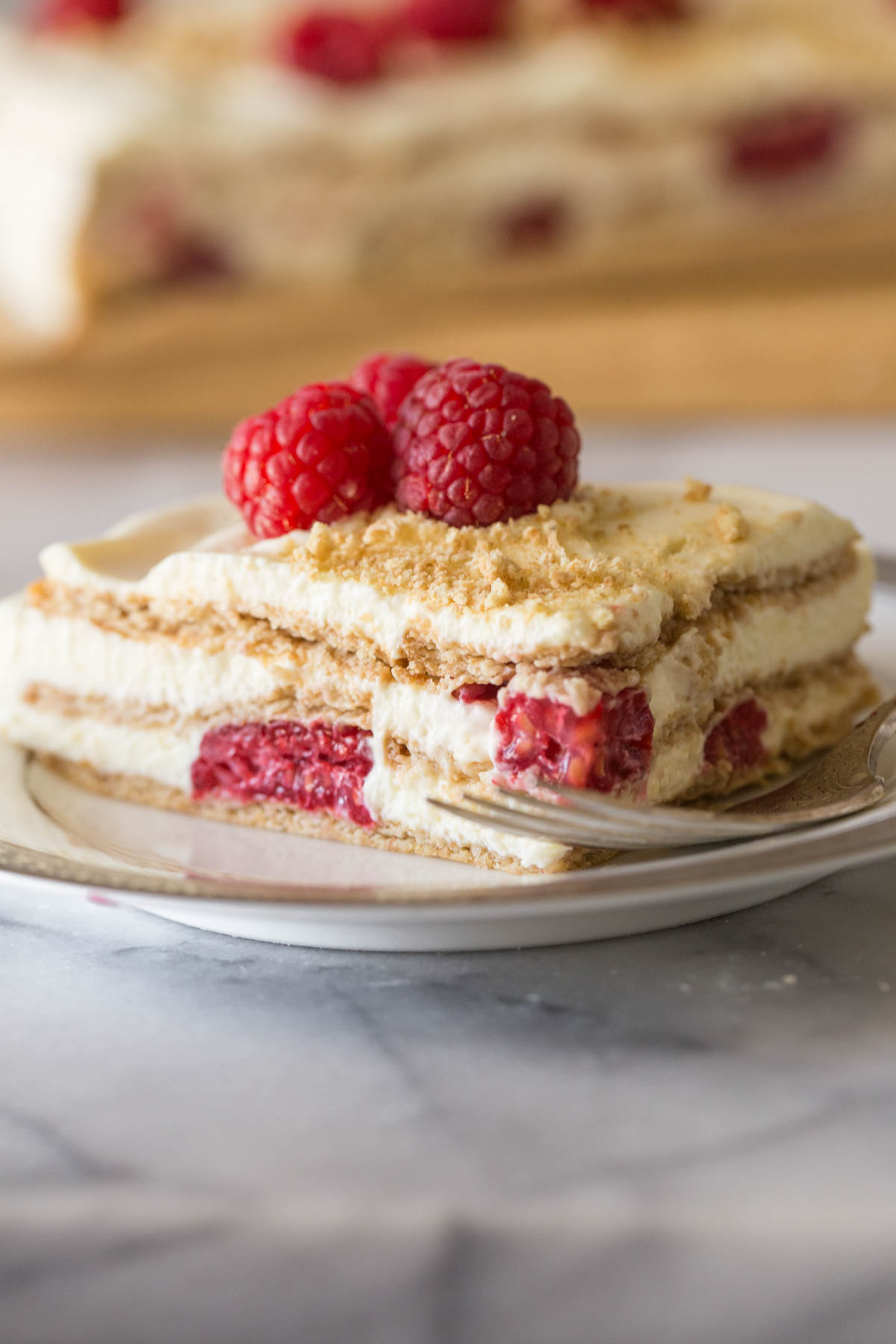Close up shot of a piece of Raspberry Icebox Cake on a plate with a fork.