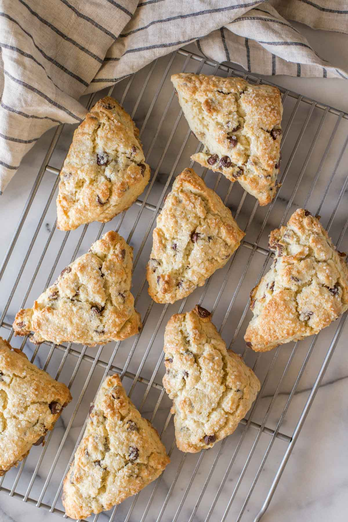 Overhead shot of Chocolate Chip Scones on a cooling rack with a marble background.