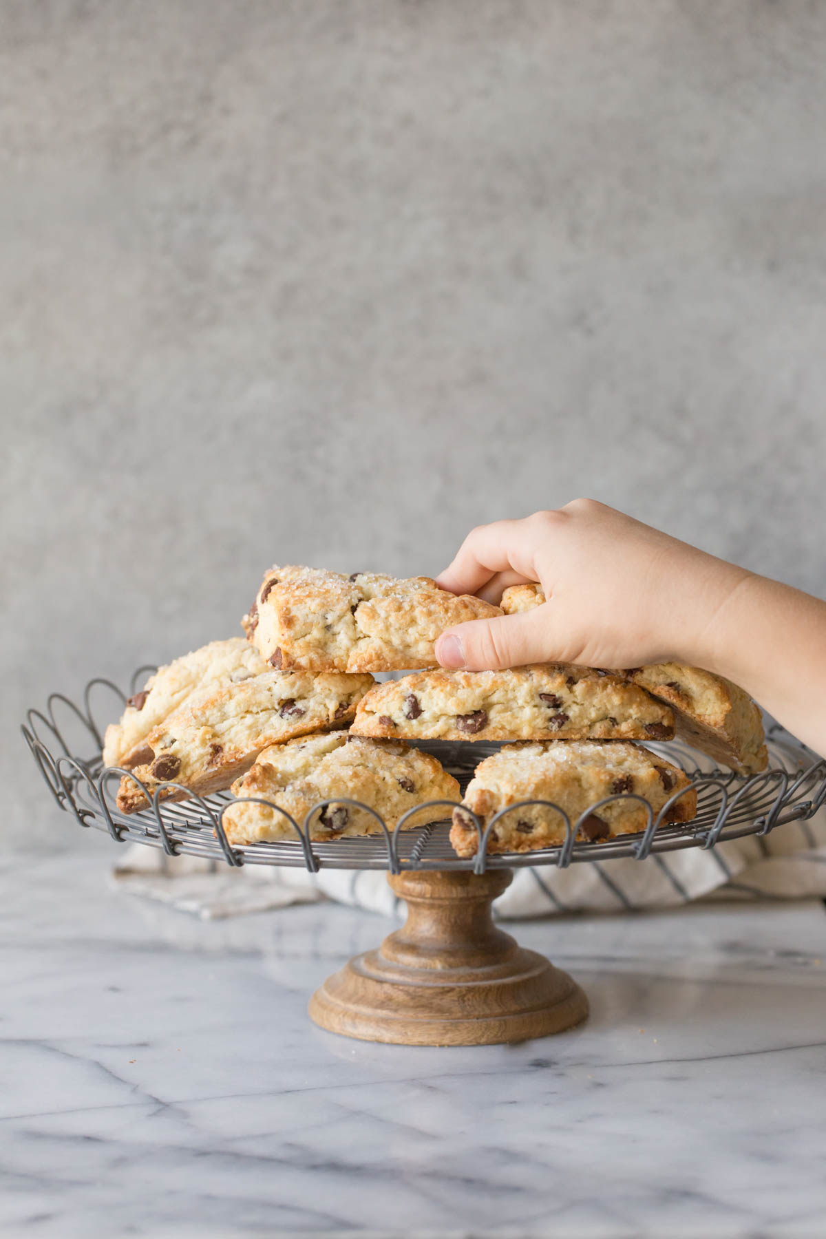 A stack of Chocolate Chip Scones on a cake stand with a hand reaching for the scone on top.