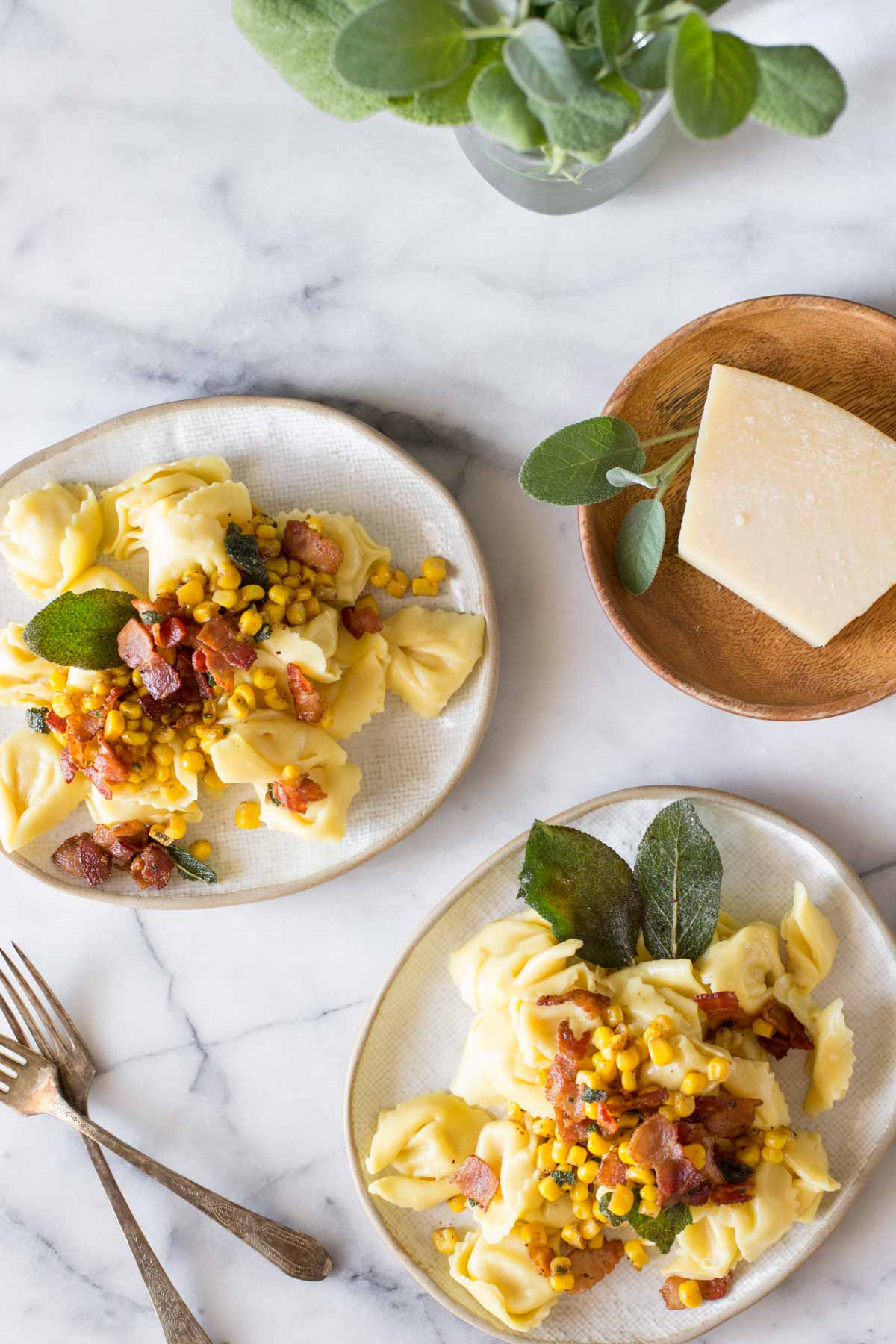 Overhead view of two plates of Creamy Tortellini With Bacon and Corn and a wooden plate with a block of Parmesan cheese, on a marble background.