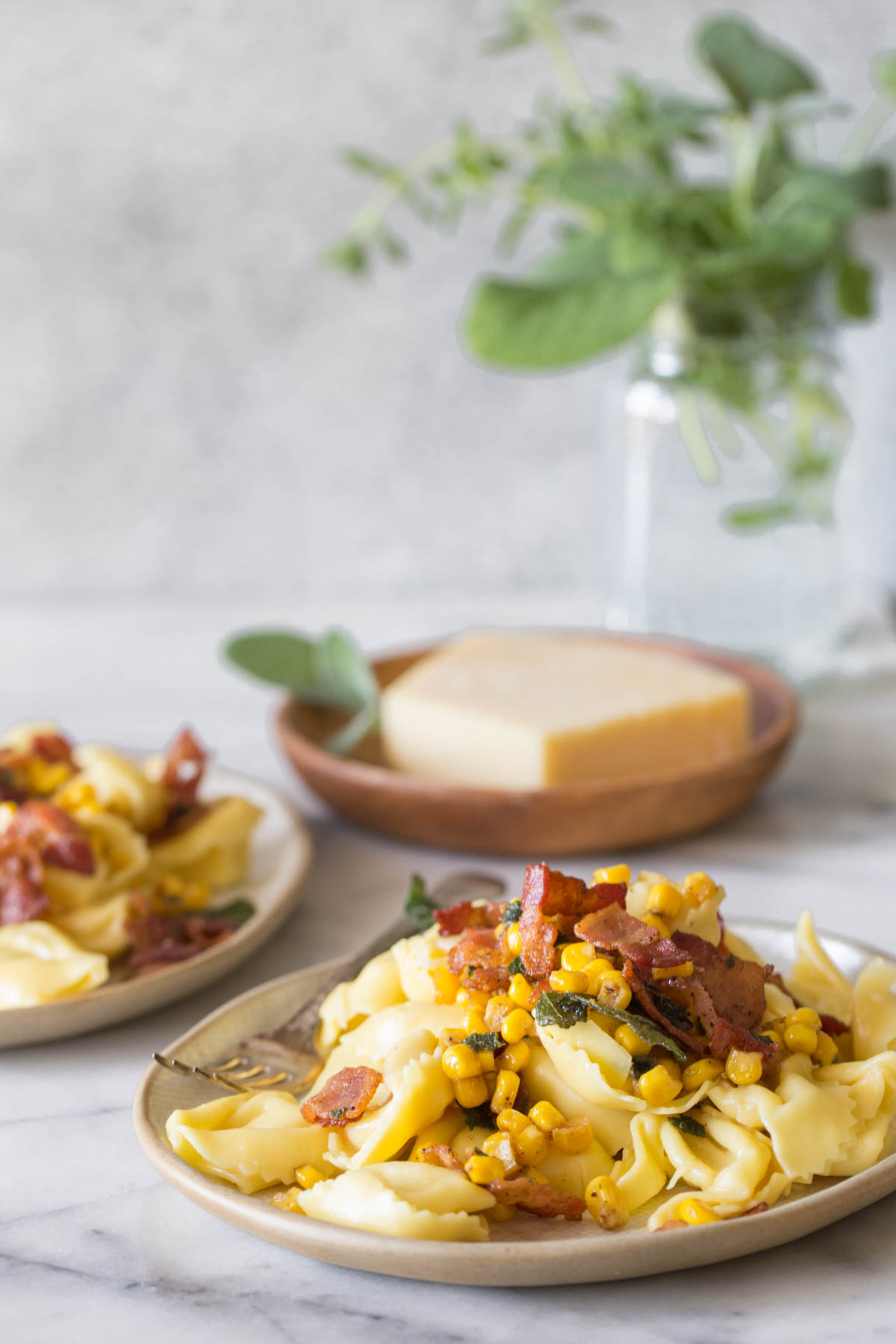 A plate of Creamy Tortellini With Bacon and Corn, and a wooden plate with a block of Parmesan cheese in the background.