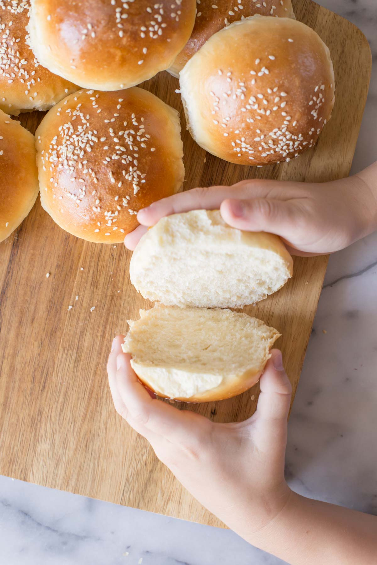 Two hands separating a cut Sourdough Hamburger Bun on a wooden cutting board with more buns next to it.