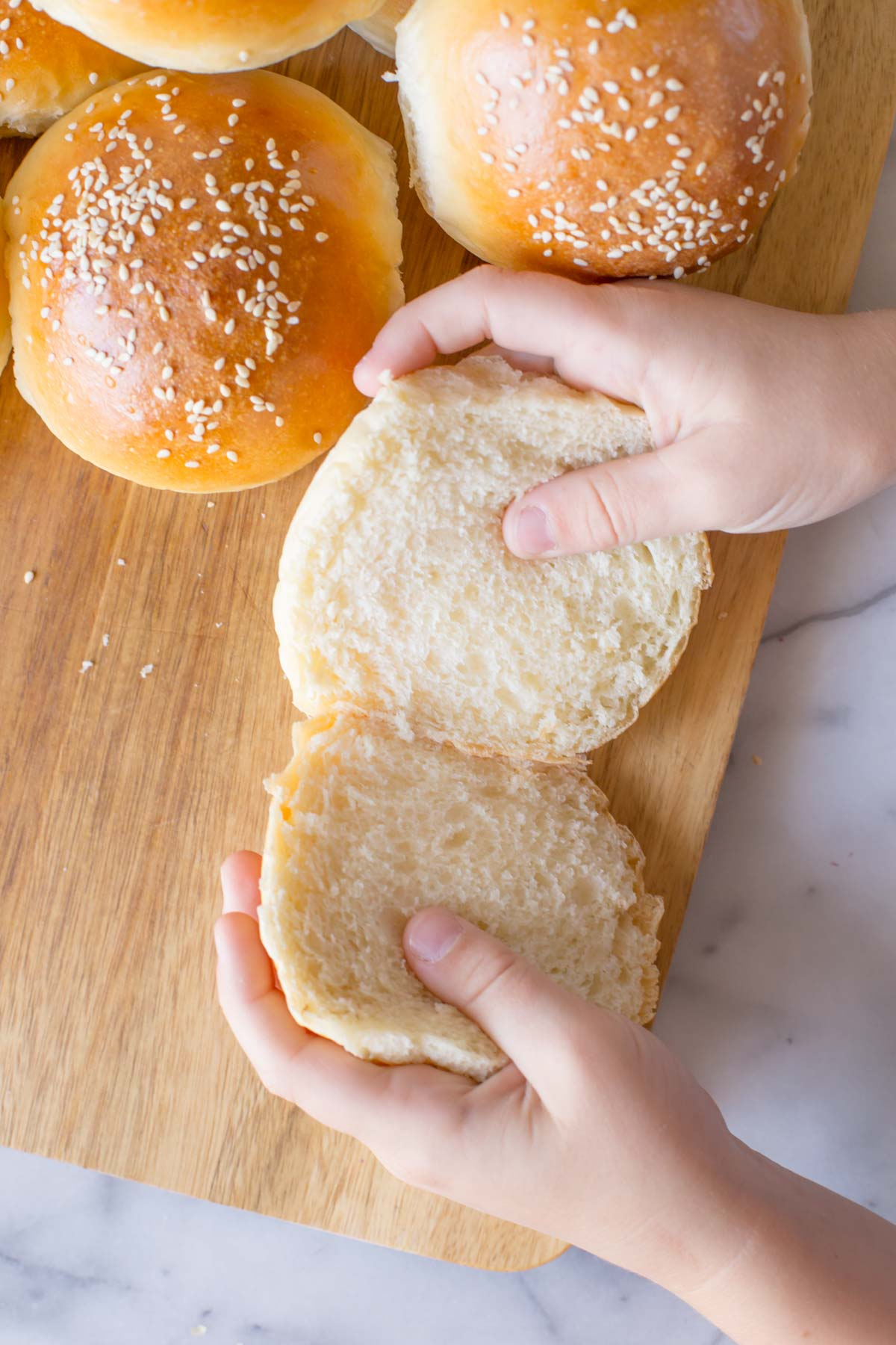 A close up shot of two hands separating a cut Sourdough Hamburger Bun on a wooden cutting board with more buns next to it.