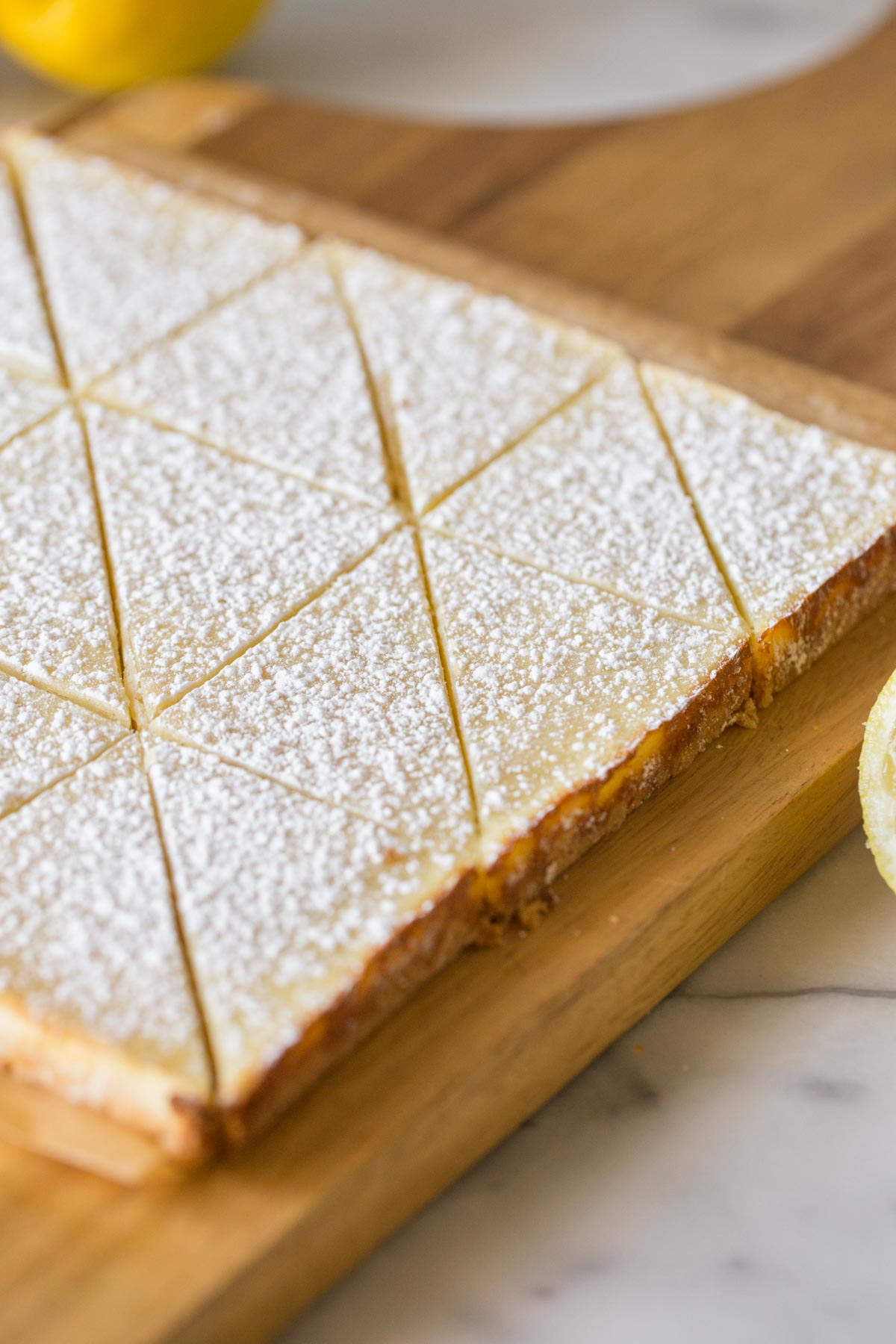 Swedish Lemon Bars on a wooden cutting board.